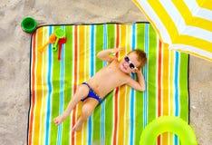 Glückliches Kind, das auf buntem Strand ein Sonnenbad nimmt Stockbilder