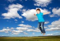 Glückliches Kind, das auf die Wiese springt Stockfotografie