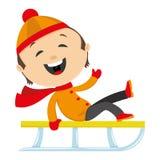 Glückliches Kind, das auf einem Schlitten sitzt Stockfoto
