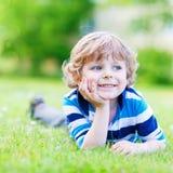 Glückliches Kind, das auf Rasenfläche und dem Träumen genießt Lizenzfreie Stockfotografie