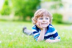 Glückliches Kind, das auf Rasenfläche und dem Träumen genießt Stockbilder