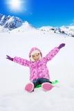 Glückliches Kind, das auf Schlitten am sonnigen Tag sitzt Lizenzfreie Stockfotos