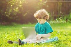 Glückliches Kind, das den Laptop sitzt auf dem grünen Gras im Sommer spielt Lizenzfreie Stockfotos