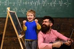 Glückliches Kind, das in der Schule Aufgabe abschließt Aufgeregter Junge, der nahe bei lächelndem Lehrer steht Spaß an der Lektio lizenzfreies stockfoto
