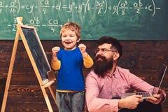 Glückliches Kind, das in der Schule Aufgabe abschließt Aufgeregter Junge, der nahe bei lächelndem Lehrer steht Spaß an der Lektio stockbilder