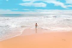 Glückliches Kind, das in die Seewelle läuft stockbild