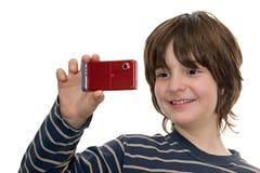 Glückliches Kind, das ein Foto mit einem Telefon nimmt Lizenzfreie Stockfotos