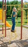 Glückliches Kind, das an einem Spielplatz spielt. Lizenzfreie Stockbilder