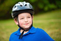 Glückliches Kind, das einen Fahrradsturzhelm trägt lizenzfreies stockfoto