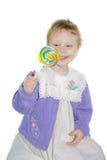 Glückliches Kind, das ihre Lutschersaugersüßigkeit betrachtet. Lizenzfreie Stockfotografie