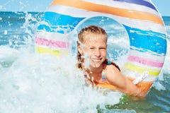 Glückliches Kind, das im blauen Wasser von Ozean auf einem tropischen Erholungsort spielt stockbilder