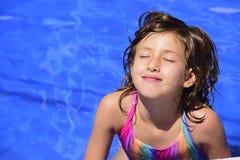 Glückliches Kind, das im Pool sich entspannt Stockfotos