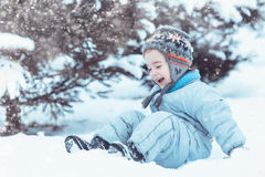 Glückliches Kind, das im Schnee spielt Stockfotografie