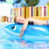 Glückliches Kind, das im Swimmingpool spielt Stockbilder