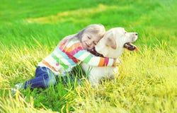 Glückliches Kind, das labrador retriever-Hund auf Gras umarmt lizenzfreies stockbild