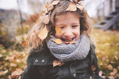 Glückliches Kind, das mit Blättern im Herbst spielt Saisonaltätigkeiten im Freien mit Kindern stockbilder