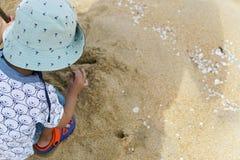 Glückliches Kind, das mit Sand am Strand im tropischen Wetter - Bild spielt stockfotografie