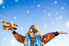 Glückliches Kind, das mit Spielzeugflugzeug im Winter spielt Stockfoto