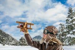 Glückliches Kind, das mit Spielzeugflugzeug spielt Stockbild