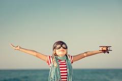 Glückliches Kind, das mit Spielzeugflugzeug spielt stockfoto