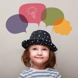 Glückliches Kind, das oben auf Ideenbirne in der Blase denkt und schaut Stockbild