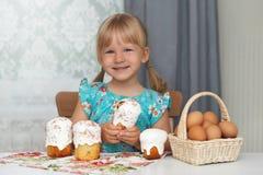 Glückliches Kind, das Ostern-Kuchen und -eier isst lizenzfreie stockfotos