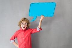 Glückliches Kind, das Papierspracheblase hält stockbilder