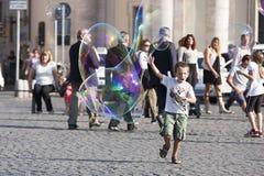 Glückliches Kind, das in Richtung zu einer Seifenblase läuft Lizenzfreie Stockbilder
