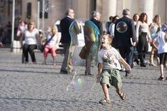 Glückliches Kind, das in Richtung zu einer Seifenblase läuft Stockbilder