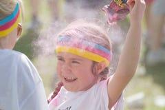 Glückliches Kind, das rosa Farbpulver über dem Kopf spritzt Stockfoto