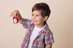 Gl?ckliches Kind, das rote Uhr auf grauem Hintergrund h?lt Kind mit Wecker lizenzfreie stockbilder