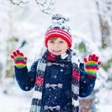 Glückliches Kind, das Spaß mit Schnee im Winter hat Stockbild