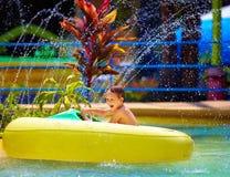 Glückliches Kind, das Spielzeugwasserboot im Aquapark fährt Lizenzfreies Stockfoto