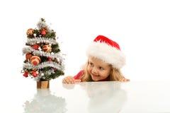 Glückliches Kind, das um einen kleinen Weihnachtsbaum lauert Lizenzfreie Stockfotos