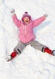Glückliches Kind, das unten die Hügel im Winterpark rollt Stockfotos