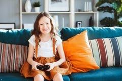 Glückliches Kind, das zu Hause Videospiele mit gamepad spielt Stockbild