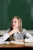 Glückliches Kind in der Schule mit Buch stockbild