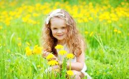 Glückliches Kind des kleinen Mädchens auf Gras mit gelbem Löwenzahn blüht im Sommer Stockbild