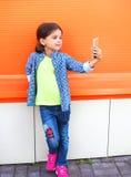 Glückliches Kind des kleinen Mädchens, das Bildselbstporträt auf Smartphone in der Stadt über buntem nimmt Lizenzfreie Stockbilder