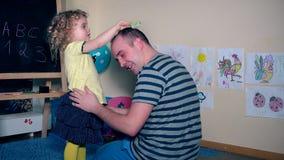 Glückliches Kind des kleinen Mädchens, das ihren halben Kahlkopf des Vatervatis bürstend kämmt stock video