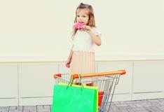 Glückliches Kind des kleinen Mädchens mit süßem Karamelllutscher und -Einkaufstaschen im Laufkatzenwarenkorb Lizenzfreie Stockfotos