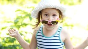 Glückliches Kind in einem Hut und Sonnenbrillelächeln und -lachen, drückt Gefühle des Glückes aus stock video