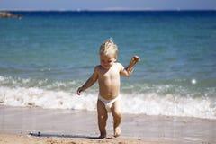 Glückliches Kind, entzückender blonder Kleinkindjunge in der Windel, spielend auf dem Strand, der in das Wasser läuft und genieße Stockbild
