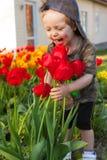 Glückliches Kind gegen Frühling blüht Hintergrund Sohn gibt der Mama eine Blume Stockfotografie