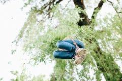 Glückliches Kind hat Spaß im Sommerpark auf einem improvisierten Schwingen lizenzfreie stockfotos