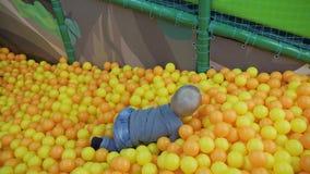 Glückliches Kind, Kinderjunge, der, Spaß auf Spielplatz mit bunten Plastikbällen im Pool habend spielt Kind, das mit buntem spiel stock video