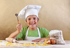 Glückliches Kind mit dem Chefhut, der Teigwaren oder Plätzchen macht Stockfotografie