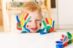 Glückliches Kind mit den gemalten Händen Stockfotografie