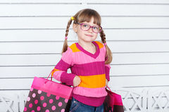 Glückliches Kind mit Einkaufstaschen. Sie genießt die Geschenke und die Feiertage Stockbilder