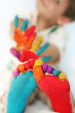 Glückliches Kind mit gemalten Füßen und den Händen Lizenzfreies Stockbild